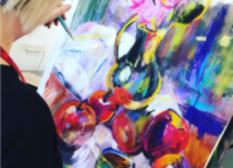 Woman painting canvas on easel