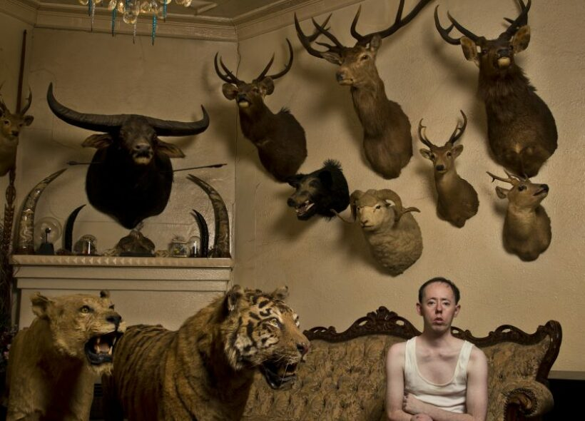 Man sitting on antique sofa in a room of taxidermied animals