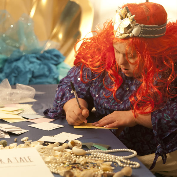 A woman writes on cards, while surrounded by props and jewellery.