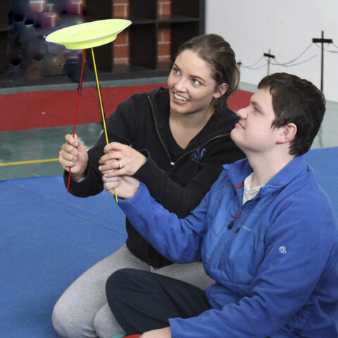 Trainer and young woman plate spinning