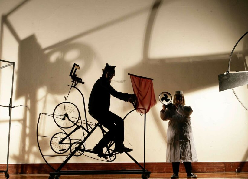 A person riding a bicycle type machine, a person holding an electric fan. Shadows cast on the wall.