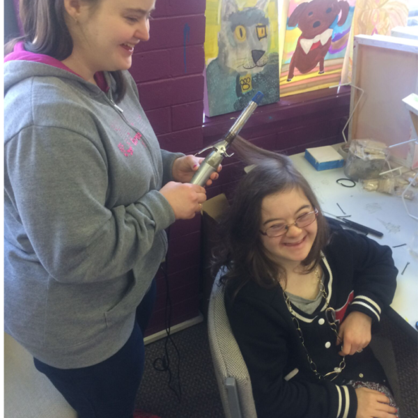 A young woman using curling tongs on another young woman'shair