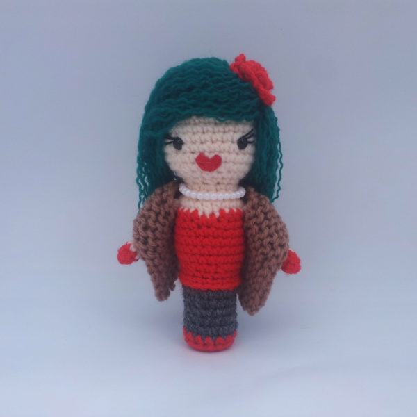 A crochet doll with blue hair. She wears a red dress, lipstick and flower in her hair and a brown jacket.