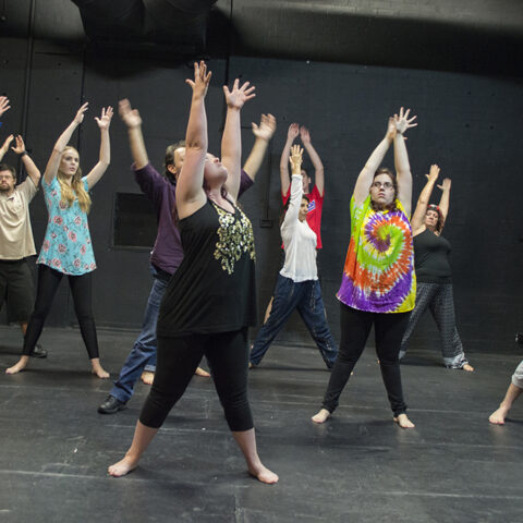 Participants at an Access Arts Theatre & Dance Ensemble workshop dancing and raising their hands up in a rehearsal space.