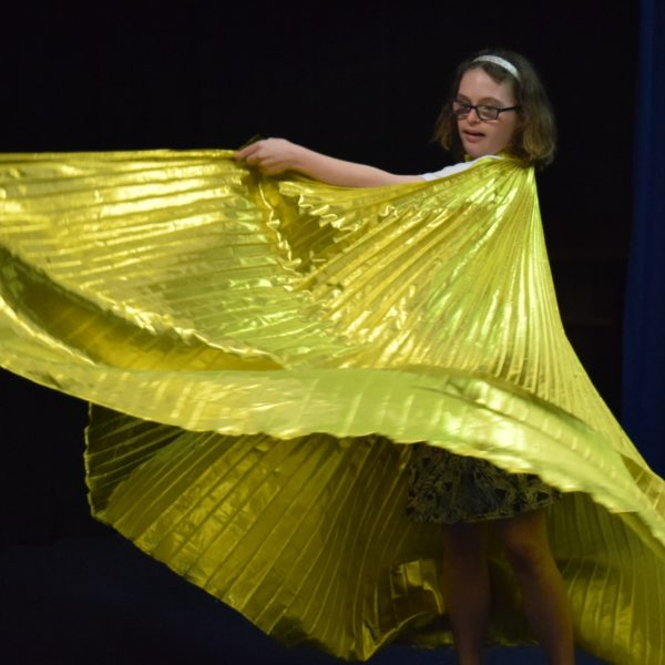 A young woman swirling a log golden cape