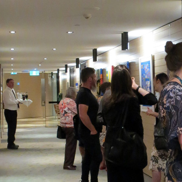 Opening night of Celebrating Difference at KPMG, Brisbane, with few people looking at the artworks hung on a corridor.