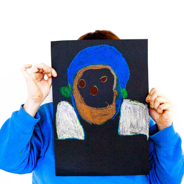 An Art + Connect workshop participant with their self-portrait.