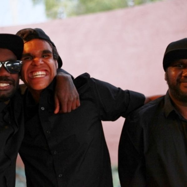 3 young smiling aboriginal men standing front of a curved pink wall