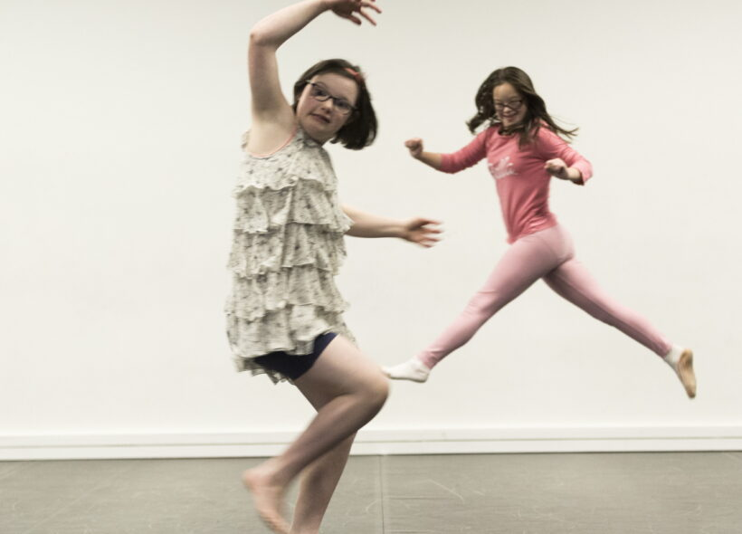 Two young girls dancing.