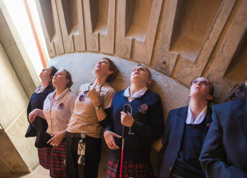 A group of blind and vision impaired students leaning against a wall and looking up.