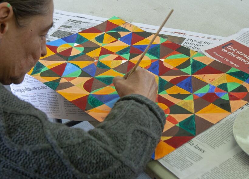 A woman painting a geometric based artwork.