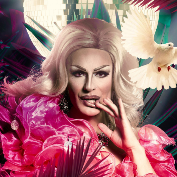 A drag performer with white-blonde hair looks at the camera with their hand near their mouth. They are wearing a ruffled pink dress, and sparkly jewellery. They are surrounded by ferns and plants. There is a disco ball hanging behind, and a white dove mid-flight to the right of the person.