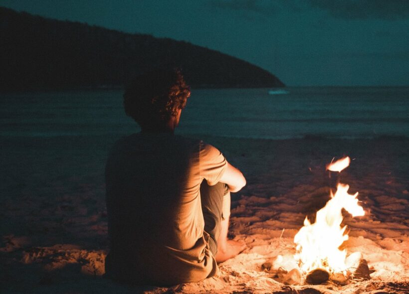 A man sits besides a small fire on beach at night