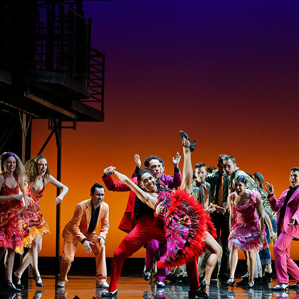 A group of people dance wearing colourful dresses and suits.