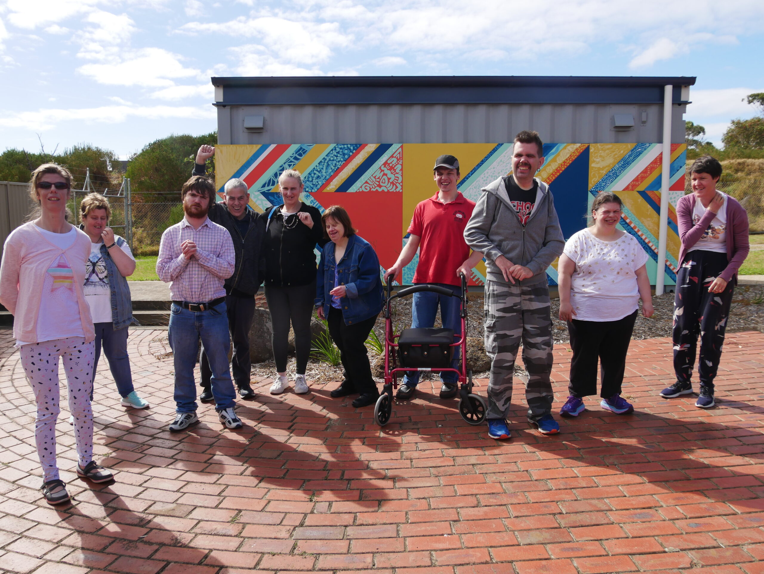 A group shot of the Art About artists infront of a brightly coloured mural.