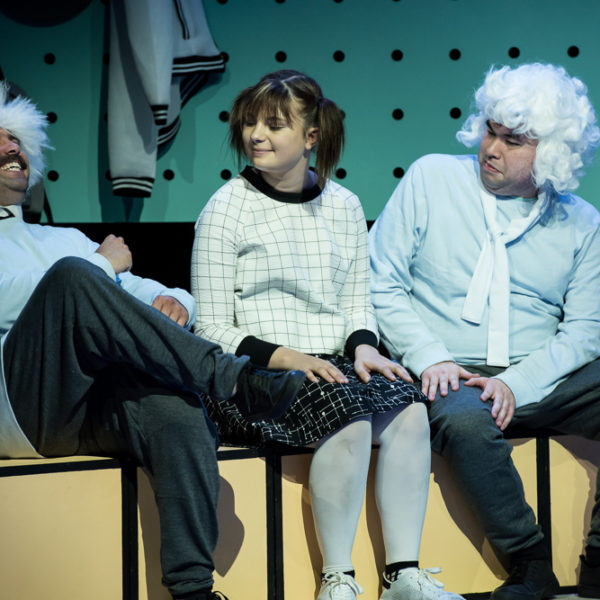 Three people sit on stage, laughing and smiling. The two men are wearing white wigs. A girl in pigtails sits in the middle.