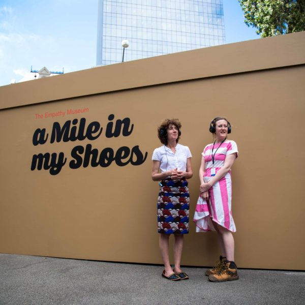 A Mile in My Shoes creative team Clare Patey & Kitty Ross standing in front of the giant shoebox, which is the size of a shipping container.