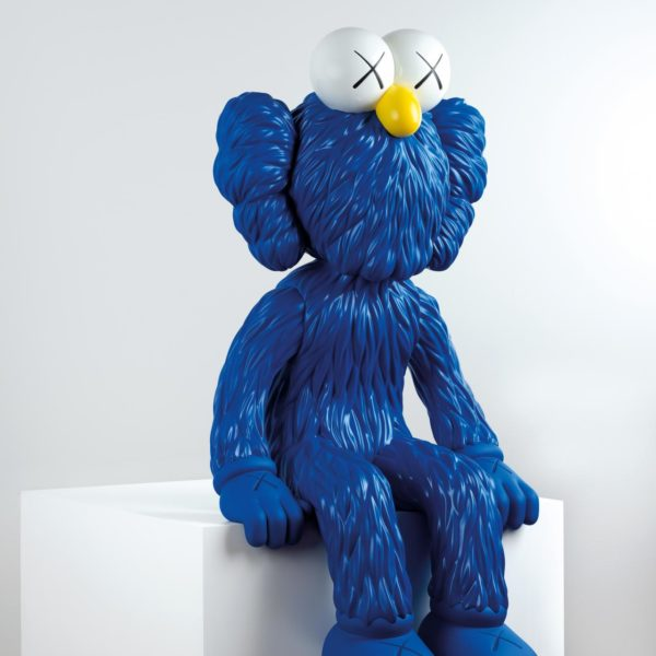 A blue bear character with large white eyes and a yellow nose.