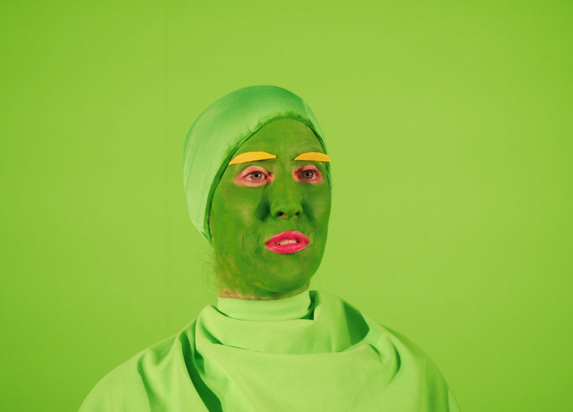 A close up shot of a performer's face in green, with yellow eye brows, wearing a green hat in front of a green background.