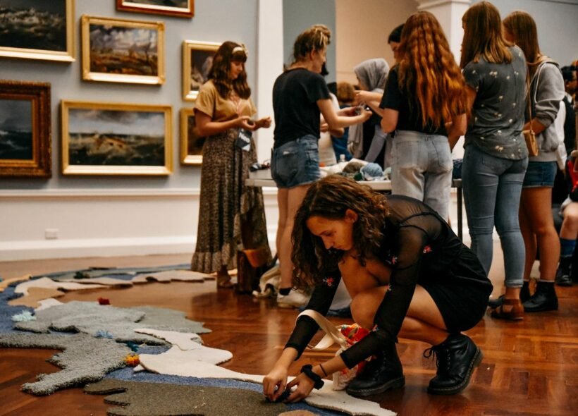 Teenagers in the Art Gallery mingling together in a group creating a collaborative work of art using carpet and felt around a table. One female crouched on the ground in the foreground piecing together some carpet on the floor.