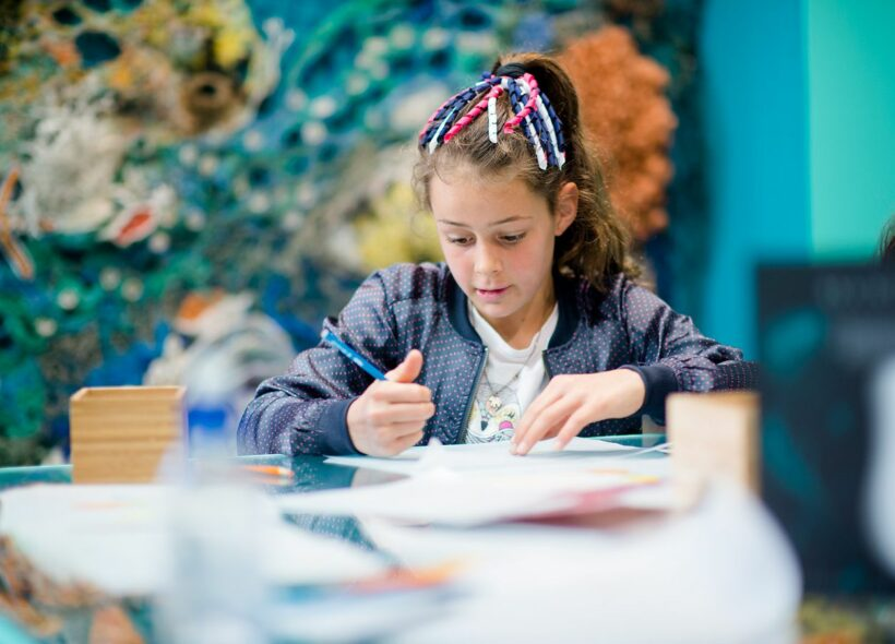 Young girl with her hair tied in ribbons sitting down with some pencils and paper looking down to draw