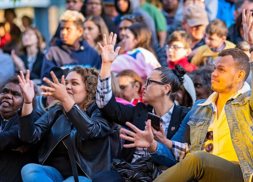 photo: by John Montesi. Audience members including Aboriginal male and females waving their hands as an Auslan sign of appreciation