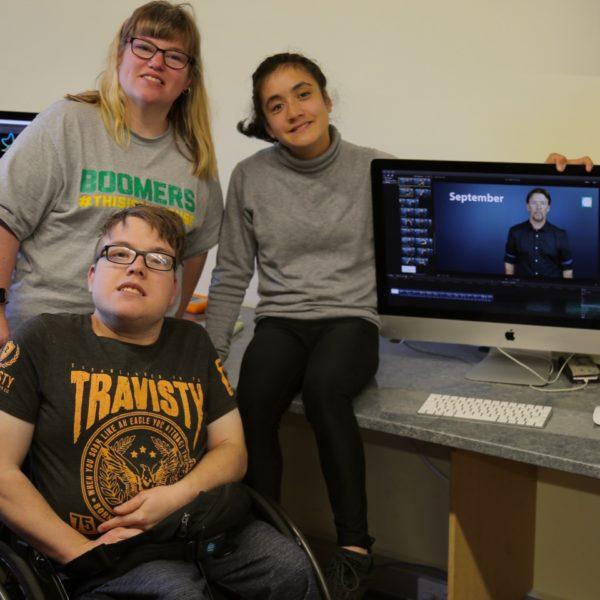 Three people sitting near computers.