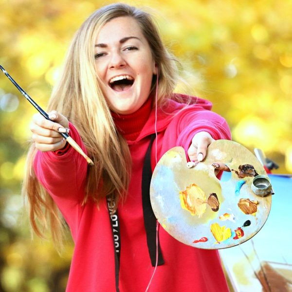 Happy young woman holding up paintbrush and paint