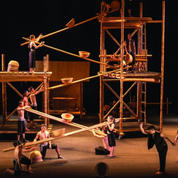 Circus performers on a stage making an impressive high structure out of bamboo poles, baskets and scaffolding