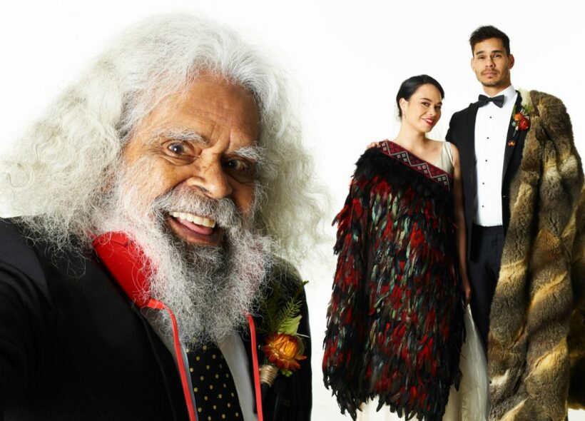Actor Uncle Jack Charles standing in foreground smiling in formal attire with young couple in the background in traditional indigenous wedding attire