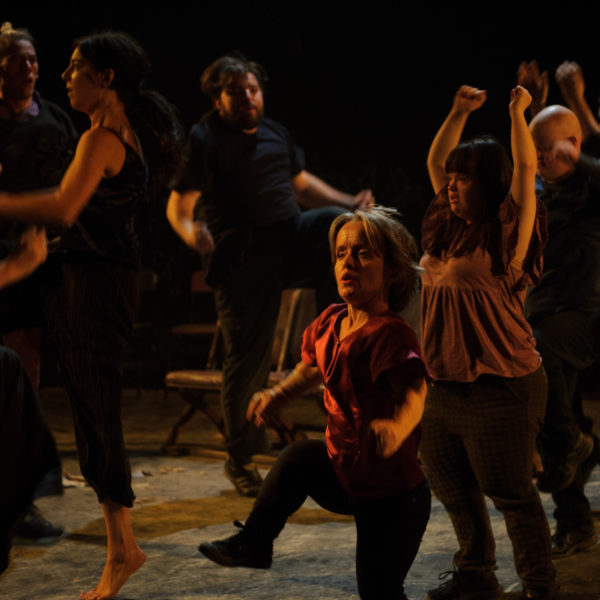 A dark image of a group of people moving and swinging their arms