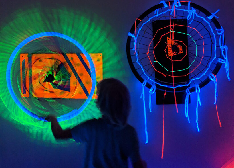 Silhouette of a child playing with glow in the dark spinning wheels.
