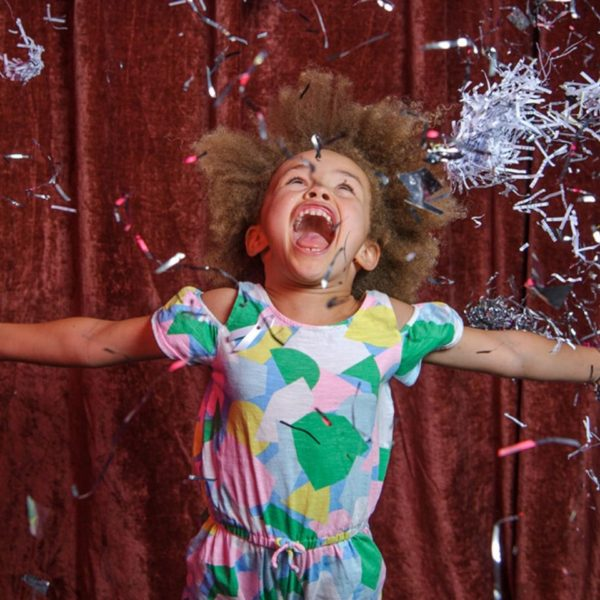 Young girl in standing in front of red curtain throwing shredded glittery paper in the air, with her mouth open and arms outstretched