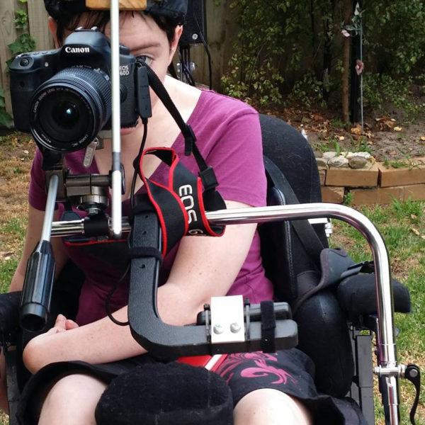 Woman in wheelchair in pink shirt looking through a camera lens