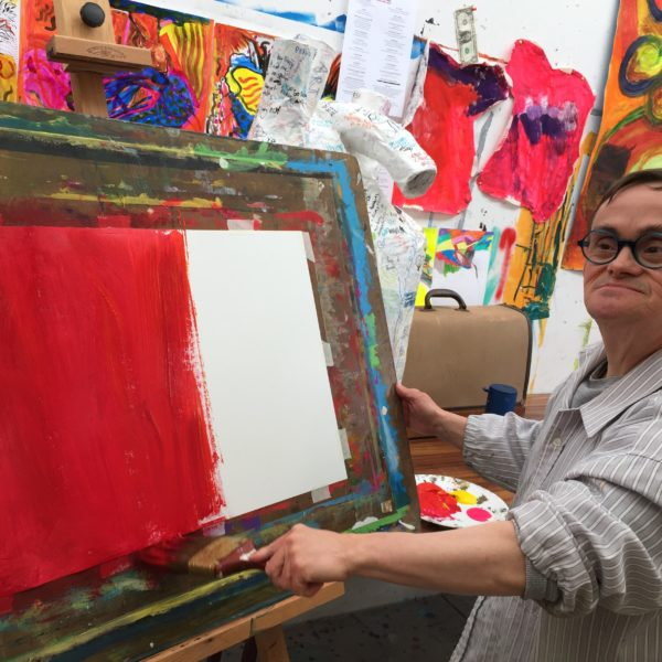 Visual artist painting in studio.