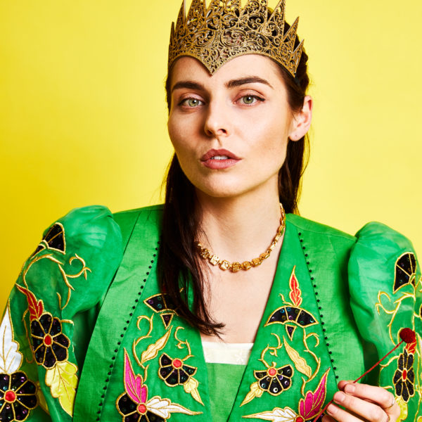 Ange Lavoipierre wears a bold crown and heavily embroidered green dress in front of a vivid yellow background.