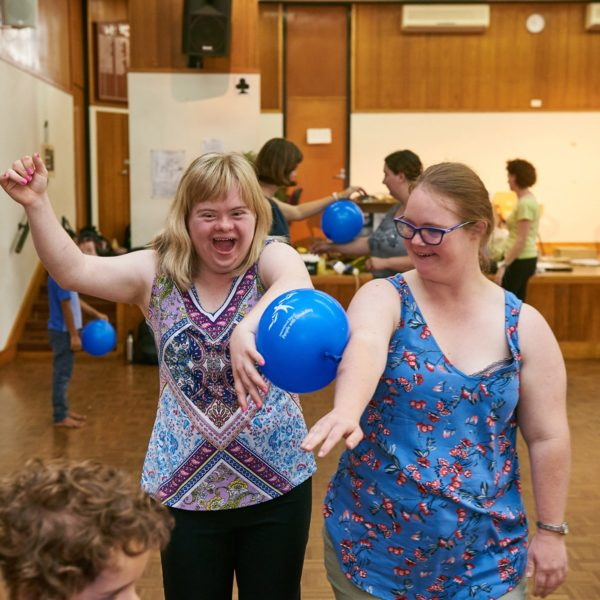 Two people laughing and holding a balloon between their arms.