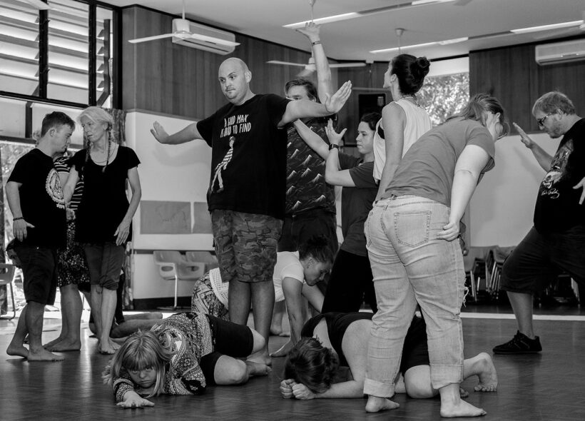 A black and white photo of a group of people in various positions. Photo credit: Leah Mclean Photography