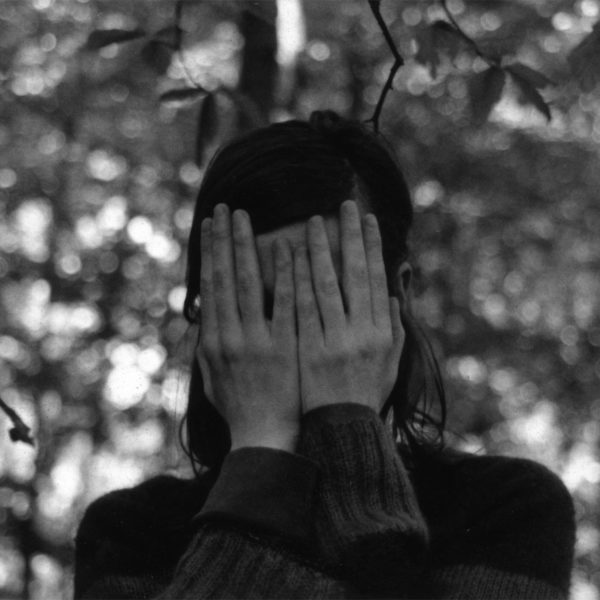 Choreographer Mette Edvardsen stands in the woods covering her face with her hands