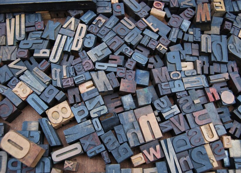 A close up of letter blocks from an old printing press, showing a jumble of different sized and shaped letters