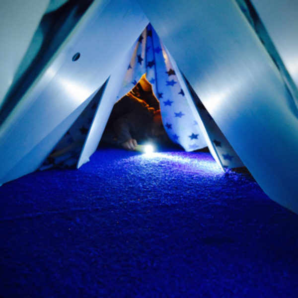 A blue blanket fort on blue carpet. In the middle of the image, a child is lying at the fort entrance shining a torch at the camera. Their face is obscured. There is warm yellow light glowing behind them.