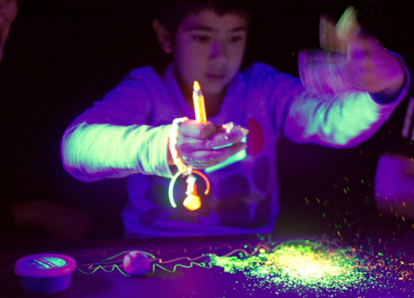 A child behind a table, looking at a pile of glowing particles, holding their hands in front of them. Their left hand is a motion blur as they are shaking it. They hold a yellow pencil and some other toys in their right hand.