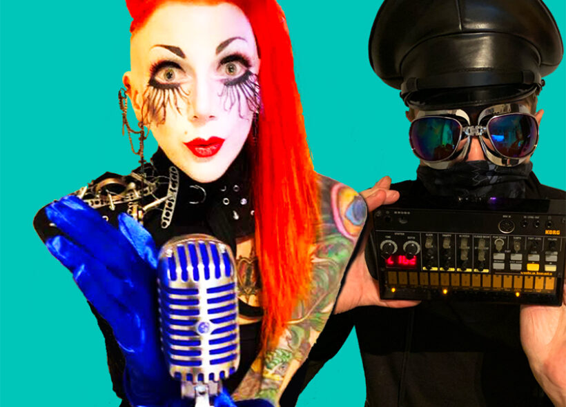 Alison and Matt both stand, against a turquoise blue background. Alison holds a Shure 55 (old-fashioned) microphone, and wears blue satin gloves, and theatrical stage makeup. Her hair is bright red, and bouffant! Matt stands to her right, wearing large black goggles, and black cap. He has a dark face-mask covering his mouth, and is holding a small Korg synthesiser.