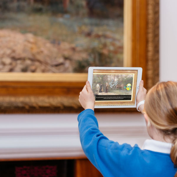 A young person holds an iPad with the Orby program, learning about Frederick McCubbin's 'A bush burial'