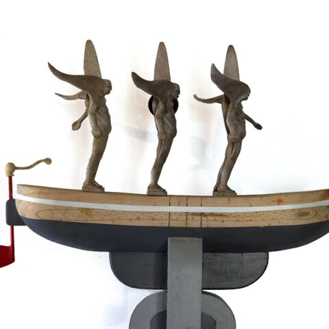 Three light brown winged male figures stand on a wooden boat like shape with the bottom painted grey. The rudder is painted red.