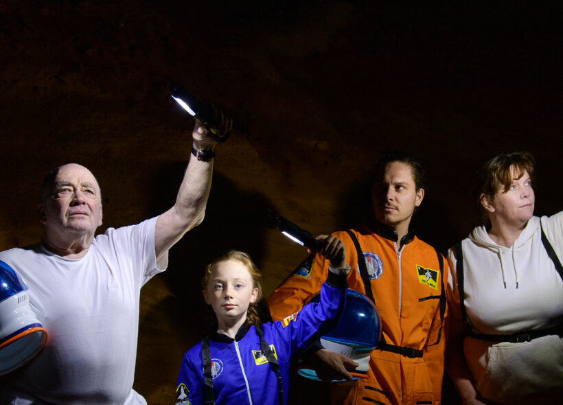 A family — man in his sixties carrying a space helmet, an 11 year old girl wearing a blue space suit, a man in his 30s in an orange space suit carrying a space helmet, and a woman in her 50s stand against an alien looking, rock wall. They hold lights aloft in the darkness.
