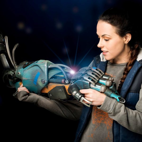 An image of a young girl holding a robot hand