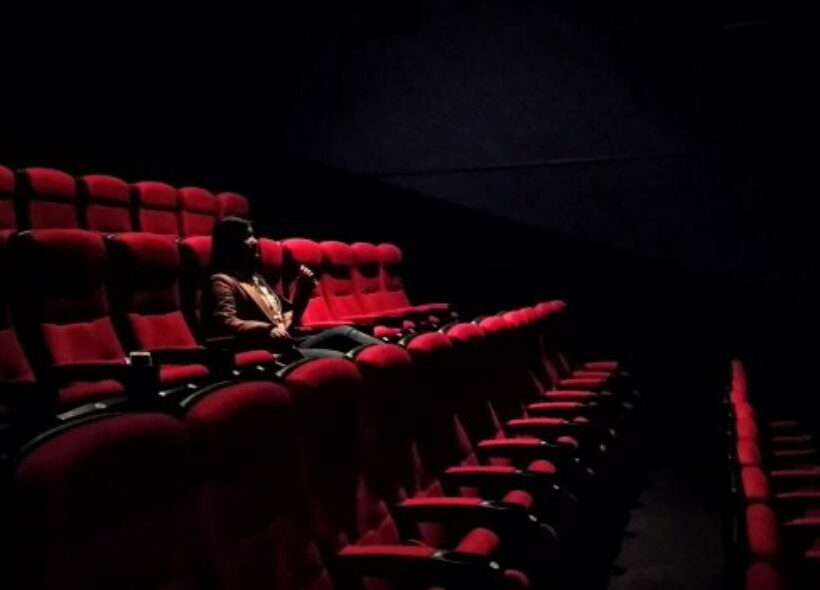 A person is sitting in a darkly lit theatre.
