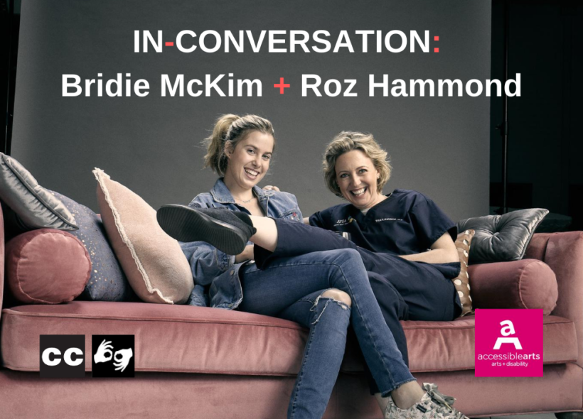 Two women are sitting on a pink velvet couch. The woman on the left has long light brown hair pulled back in a ponytail and is wearing denim jeans and jacket. The woman on the right has mid length light brown hair and is wearing a navy blue top and pants.