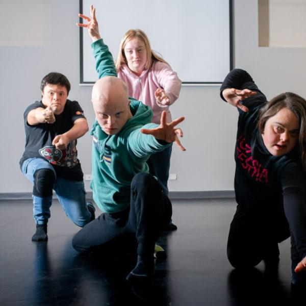 Four dancers reach their hands towards the camera